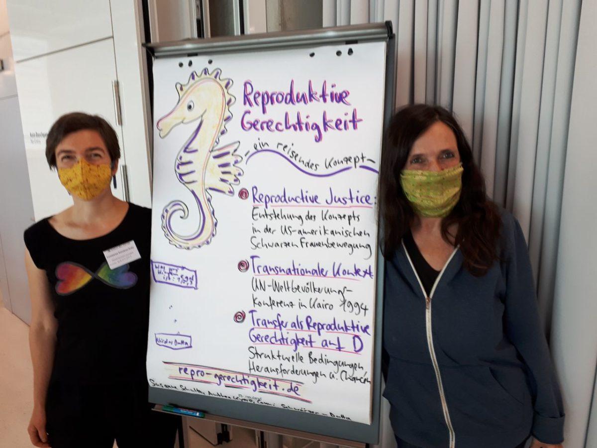 Zwei Personen, in der Mitte ein Plipchart mit einer Zeichnung von einem Seepferdchen und der Überschrift Reproduktive Gerechtigkeit